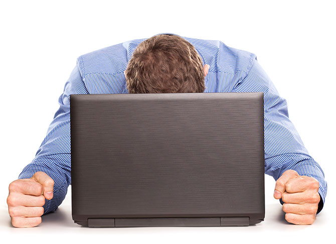 Man with head down and balled fists frustrated with computer